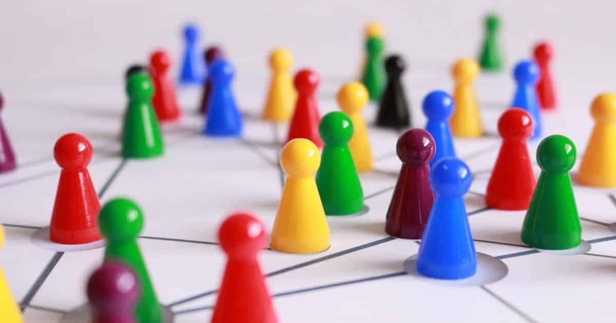 Optimize social media experience on LinkedIn, small colorful board game pieces scattered on a table